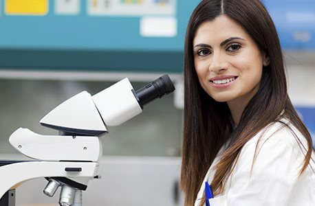 Scientist with microscope in lab coat smiling