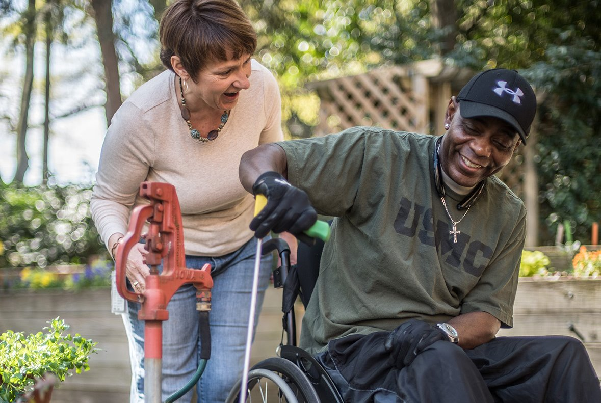 happy patient exploring outside with  another individual's support