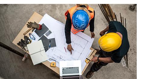 Two men reviewing blueprints at construction site