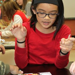 Students enjoy hands-on science experiments that also strengthen their Spanish language learning.