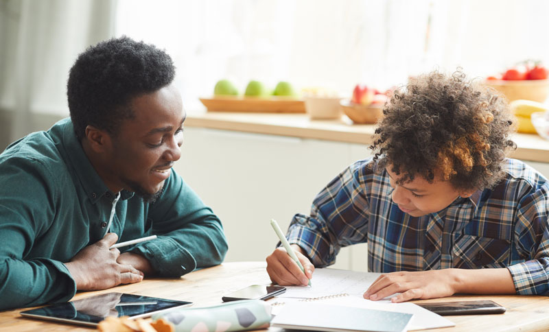 African father helping to his son to study during online education at home man explaining the material while boy making notes in notebook