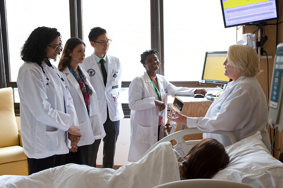 Image of Doctor talking to a room of medical students while a patient lays down near by