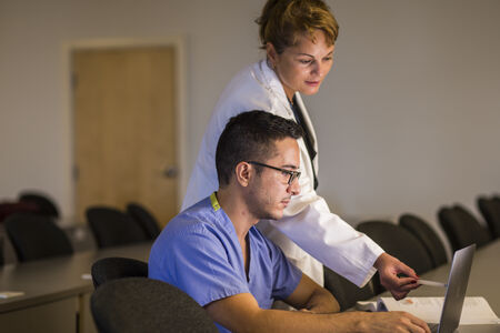Doctor and student over laptop