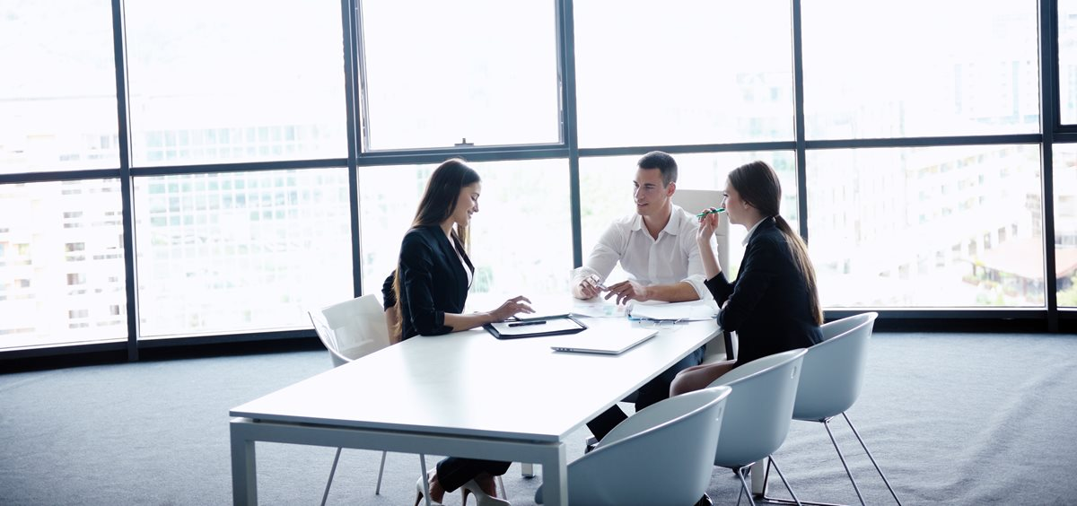 Image of three business people at a conference table.